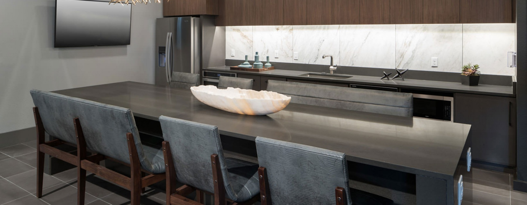 stylized light fixture hangs over long dining table in clubhouse kitchen
